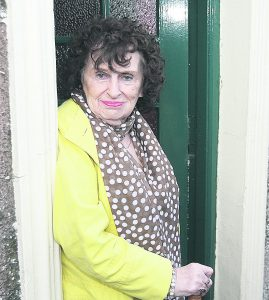 Phyllis McKenna pictured last year watching the Muff festival parade from the front door of her Main Street home.