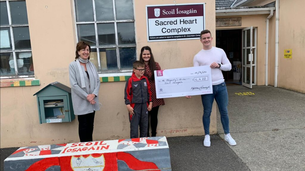 Matthew Cavanagh presents €4,488 to the Scoil Iosgain ASD class. He raised the sum by running four miles every four hours over a 48-hour period. Included are Sinead McLaughlin, principal, with Matthew's godson Caolan Costello and Ms Hegarty